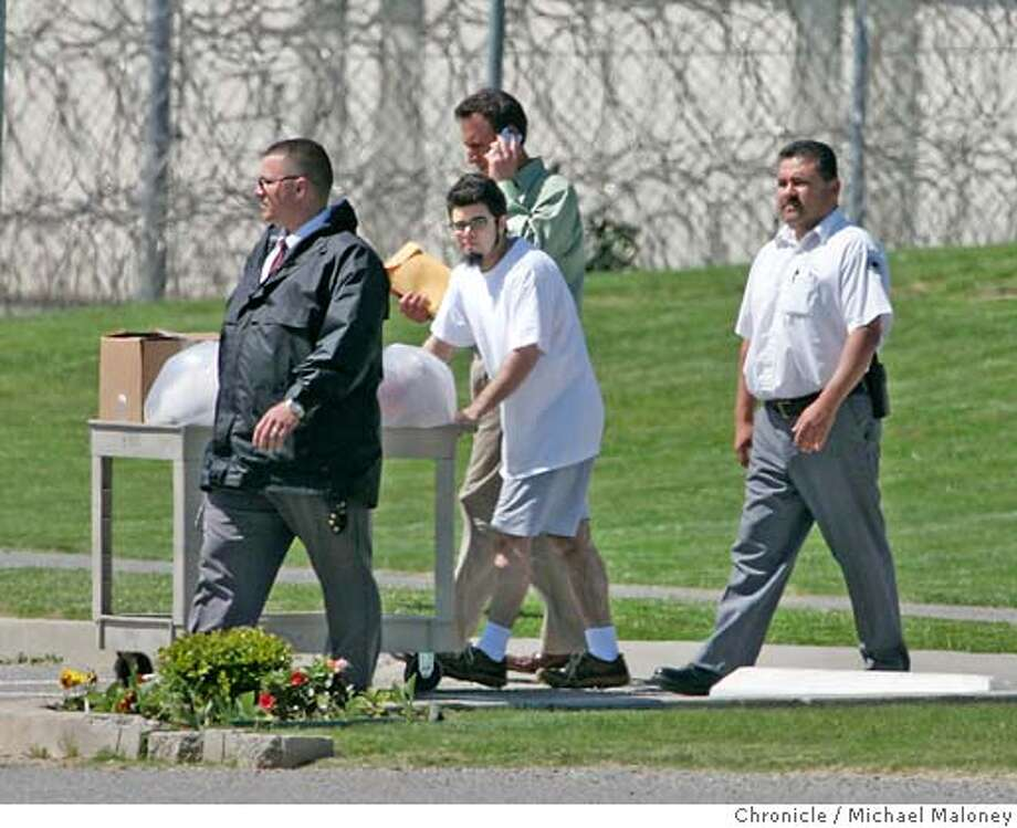 Flanked by two prison officials, Josh Wolf (center) pushes a cart full of his belongings (mostly books and letters) outside the gates to Federal Correctional Institution in Dublin. Behind him is one of his attorney's David Greene of the First Amendment Project who was there to pick Wolf up. Josh Wolf, a blogger and freelance journalist who has spent 7 1/2 months in federal prison for defying a grand jury subpoena related to his coverage of an anarchist protest, has turned over video footage to prosecutors and was released today, April 3, 2007 from the Federal Correctional Institution in Dublin. Photo by Michael Maloney / San Francisco Chronicle ***Josh Wolf, David Greene Photo: Michael Maloney