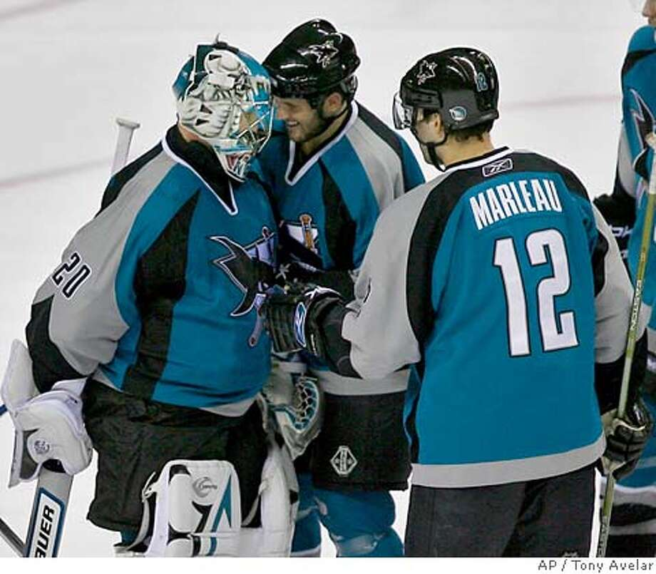 San Jose Sharks' Patrick Marleau, right, and Mark Bell, center, congratulate goalie Evgeni Nabokov, of Kazakhstan, after beating the Los Angeles Kings 6-2 in an NHL hockey game in San Jose, Calif., Sunday, April 1, 2007. (AP Photo/Tony Avelar) EFE OUT Photo: Tony Avelar