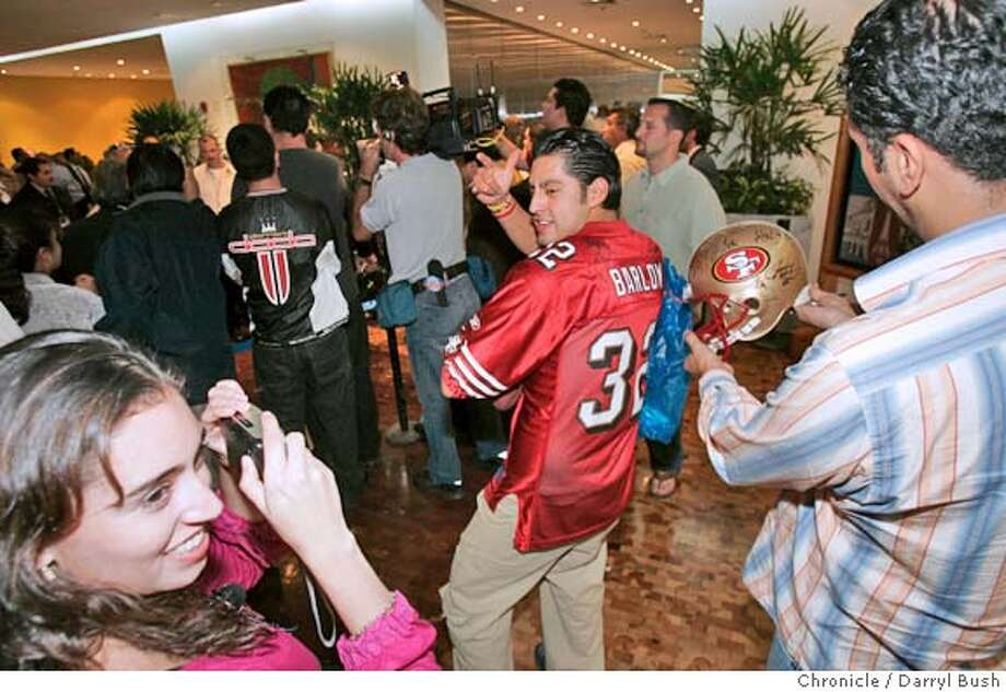 49ersmexico01_008_db.jpg  Local fans from left: Jessica Smith, Eduardo Garcia, and Elliot Smith (holding helmut) all from Mexico City, take photos of their newly autographed items as the San Francisco 49ers team arrives at the Presidente Intercontinental Hotel Mexico City, as fans show out in force to greet them.  Event on 9/30/05 in Mexico City.  Darryl Bush / The Chronicle MANDATORY CREDIT FOR PHOTOG AND SF CHRONICLE/ -MAGS OUT Photo: Darryl Bush