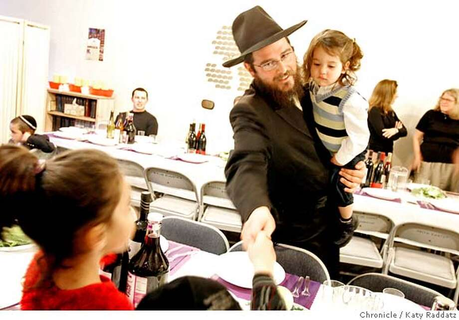 PASSOVER_004_RAD.jpg SHOWN: Rabbi Potash, holding his young son 4-yr-old Yakov Potash, greets guests as they seat themselves for the d Seder dinner. Passover dinner at the Chabad Jewish Center. These pictures were made on Monday, April. 2, 2007, in San Francisco, CA.  (Katy Raddatz/The Chronicle)  **Rabbi Potash, Seder, Yakov Potash Mandatory credit for the photographer and the San Francisco Chronicle. No sales; mags out. Photo: Katy Raddatz