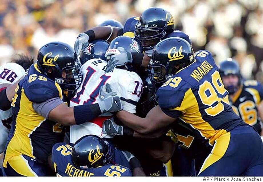 Arizona running back Mike Bell (11) is swarmed by California defenders in the second half on Saturday, Oct. 1, 2005, in Berkeley, Calif. California won, 28-0. (AP Photo/Marcio Jose Sanchez) Ran on: 10-02-2005  Cal's Marshawn Lynch leaps through the arms of Arizona's Dane Krogstad into the end zone in the first quarter and the Bears never looked back. Photo: MARCIO JOSE SANCHEZ