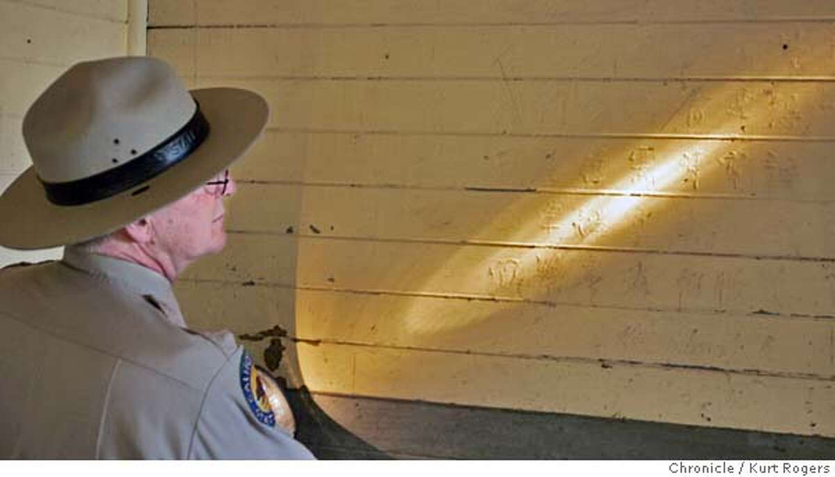 Park superintendent Roy McNamee holds a flash light to give the figures etched into the walls of the barracks . A $50 million program to preserve the historic Immigration Station on Angel Island, or what has been called the Ellis Island of the West. The first phase of the work focuses on protecting the famous poems etched into the barrack walls nearly 100 years ago by Chinese immigrants. ANGELISLAND27_0123_kr.JPG 9/27/05 in TIBURON,CA. KURT ROGERS/THE CHRONICLE MANDATORY CREDIT FOR PHOTOG AND SF CHRONICLE/ -MAGS OUT