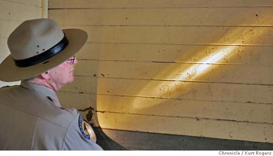 Park superintendent Roy McNamee holds a flash light to give the figures etched into the walls of the barracks . A $50 million program to preserve the historic Immigration Station on Angel Island, or what has been called the Ellis Island of the West. The first phase of the work focuses on protecting the famous poems etched into the barrack walls nearly 100 years ago by Chinese immigrants. ANGELISLAND27_0123_kr.JPG 9/27/05 in TIBURON,CA.  KURT ROGERS/THE CHRONICLE MANDATORY CREDIT FOR PHOTOG AND SF CHRONICLE/ -MAGS OUT Photo: KURT ROGERS