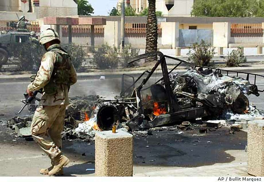 A US soldier checks the still-smoldering after an RPG (Rocket Propelled Grenade) attack Thursday July 3, 2003 in Baghdad, Iraq. According to witnesses, one soldier was wounded and an Iraqi bystander was killed. Insurgents have stepped up their attacks in recent days, hurling grenades, ambushing convoys and shooting troops patrolling the streets and bringing to 26 the number of U.S. soldiers killed in hostile fire since President Bush declared an end to major combat on May 1.(AP Photo/Bullit Marquez) Photo: BULLIT MARQUEZ