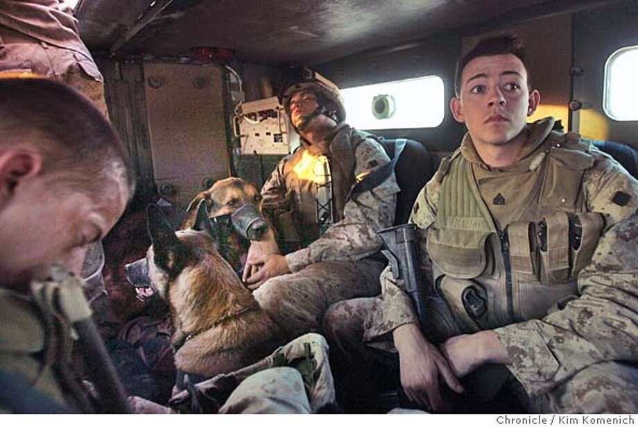 """IRAQ02_BORDER_0025_KK.JPG  At dawn Saturday, L to R, Lance Corporal Michael Biron, Corporal Courtney Hunt of Barstow, Calif sleep while Sgt Neil Fucci of Barstow, Calif is wide awake in a six-wheel drive """"cougar"""" armored vehicle on the way to Sada. Hunt and Fucci are military dog handlers and Fucci's dog """"Rambo"""" faces away from camera. Hunt's dog """"Bak"""" wears a muzzle and faces camera  Marines from the Lima Company 3rd Battalion, 6th Marines Regiment, attached to the 2nd Regimental Combat Team begin """"Operation Iron Fist"""" by performing house-to-house searches in the town of Sada, on the Iraq Syrian Border. San Francisco Chronicle Photo by Kim Komenich  10/1/05 Photo: Kim Komenich"""
