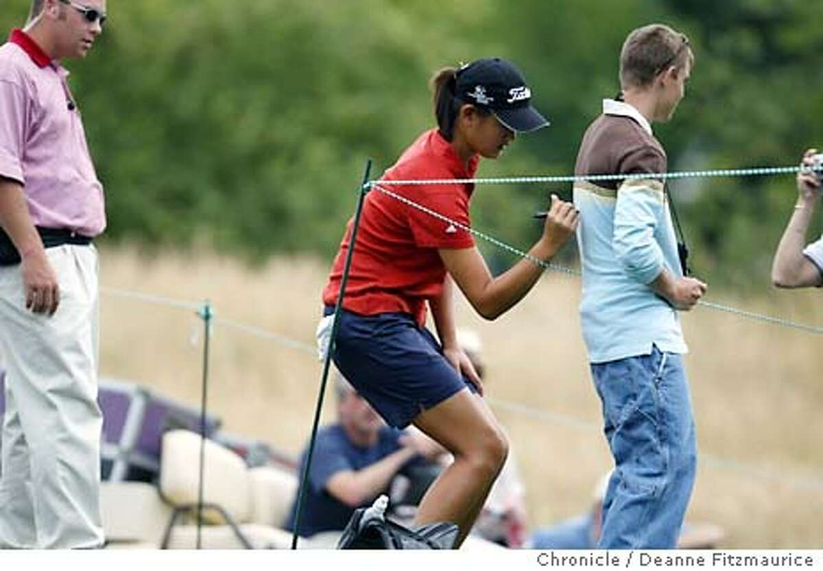 Michelle Wie, 13, is a promising young golf player. She stops to sign an autograph on the back of Chase Brummett from Delphi, Indiana on her way to the 8th tee while playing in the practice rounds of the 2003 U.S. Women's Open Championship before the tournament in North Plains, Oregon. Shot on 7/1/03 in North Plains. DEANNE FITZMAURICE / The Chronicle