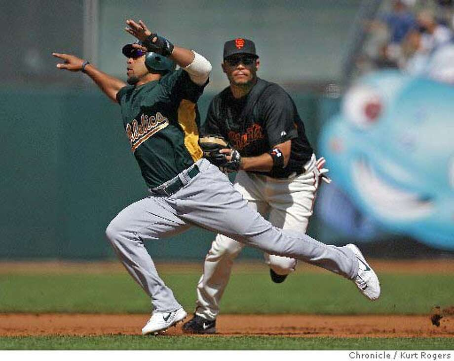 Hiram Bocachica is tagged by Giants third baseman Pedro Feliz during the A's 6-4 exhibition win Saturday. Chronicle photo by Kurt Rogers