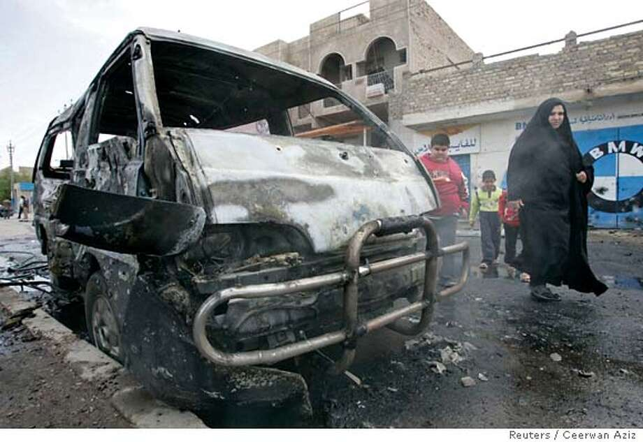 Residents walk past a burnt vehicle after a car bomb attack in Baghdad April 2, 2007. A car bomb killed two people and wounded nine others in the southern Bayaa district of Baghdad, police said. REUTERS/Ceerwan Aziz (IRAQ) 0 Photo: CEERWAN AZIZ