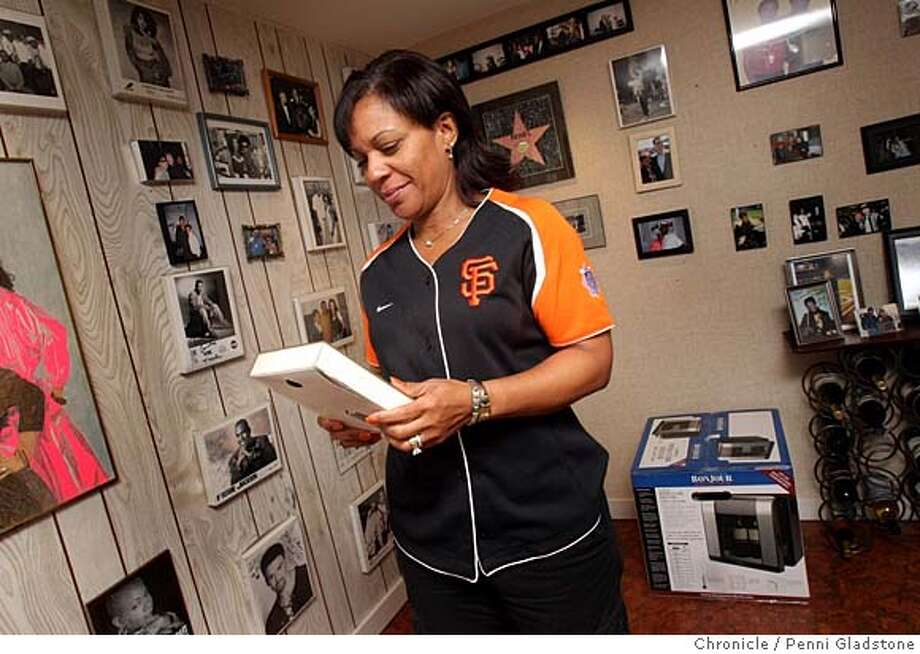 AT_HOME_RENEL  Renel looks at a photograph in a room filled with many memories. Renel Brooks-Moon the morning D.J. on KISS FM, and also the announcer at the SF Giants home games.  Event on 3/14/07 in San Francisco.  penni gladstone / The Chronicle Photo: Penni Gladstone