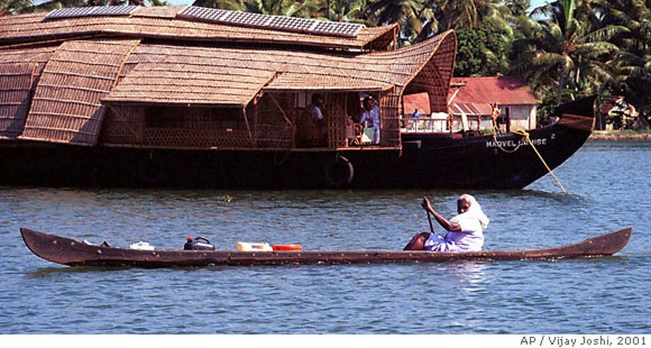 A woman paddles past a houseboat in the backwaters of southern India's Kerala state, in this January 2001 photo. Kerala state is the latest star on India's tourist map, long dominated by the Taj Mahal. Kerala's tropical beaches, mist-clad hills, unique cuisine and distinctive dance forms are some of the draws, but the most powerful is a cruise through the labyrinthine backwaters on a hand-crafted boat. (AP Photo/Vijay Joshi) Photo: VIJAY JOSHI