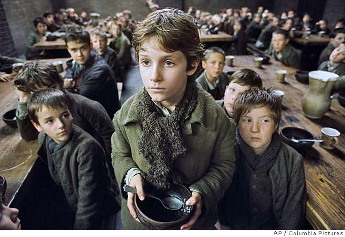 In this photo provided by Columbia Pictures, orphaned at an early age, Oliver Twist (Barney Clark) is forced to live in a workhouse lorded over by the awful Mr. Bumble, who cheats the boys of their meager rations in Columbia Pictures'
