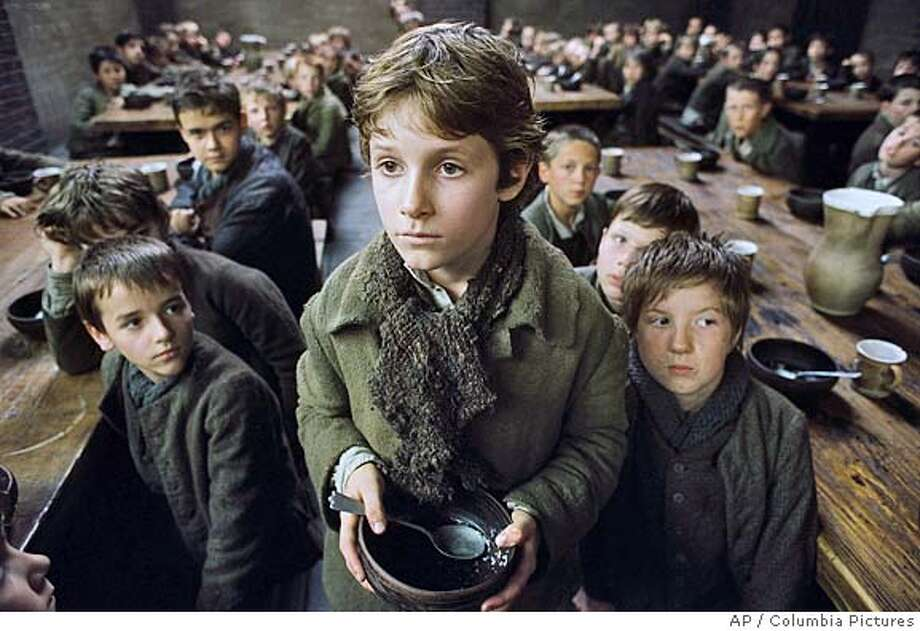 "In this photo provided by Columbia Pictures, orphaned at an early age, Oliver Twist (Barney Clark) is forced to live in a workhouse lorded over by the awful Mr. Bumble, who cheats the boys of their meager rations in Columbia Pictures' ""Oliver Twist,"" directed by Roman Polanski. (AP Photo/Columbia Pictures) Photo: Columbia"