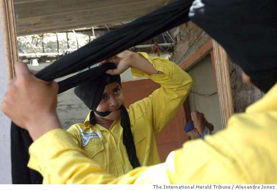 (NYT80) AMRITSAR, India -- March 28, 2007 -- SIKHS-TURBANS -- Karan Singh, 15, wraps his head with the help of Jaswinder Singh at a turban clinic run by a Sikh heritage group in Amritsar, India, on March 21, 2007. Sikh spiritual leaders express dismay at the rapidity with which a new generation of young men are trimming their hair and abandoning the turban, the most conspicuous emblem of the Sikh faith. (Alexandra Jones/The International Herald Tribune) Photo: ALEXANDRA JONES