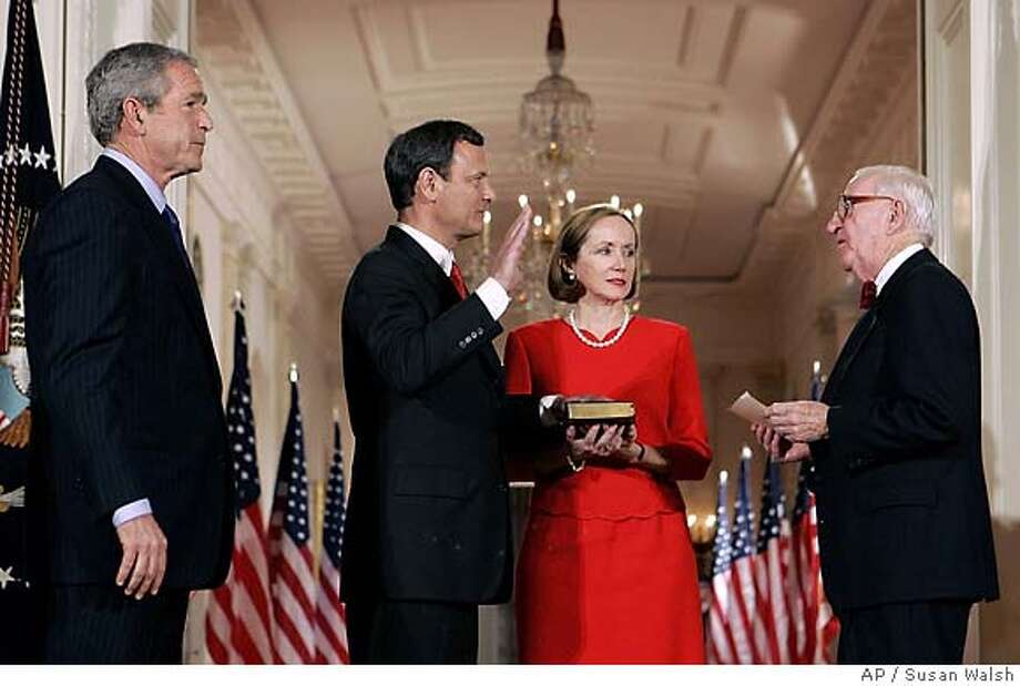 President Bush looks on as John Roberts is sworn in by Justice John Paul Stevens as 17th Chief Justice of the United States in the East Room of the White House, Thursday, Sept. 29, 2005. Roberts' wife Jane holds the Bible. (AP Photo/Susan Walsh) Photo: SUSAN WALSH