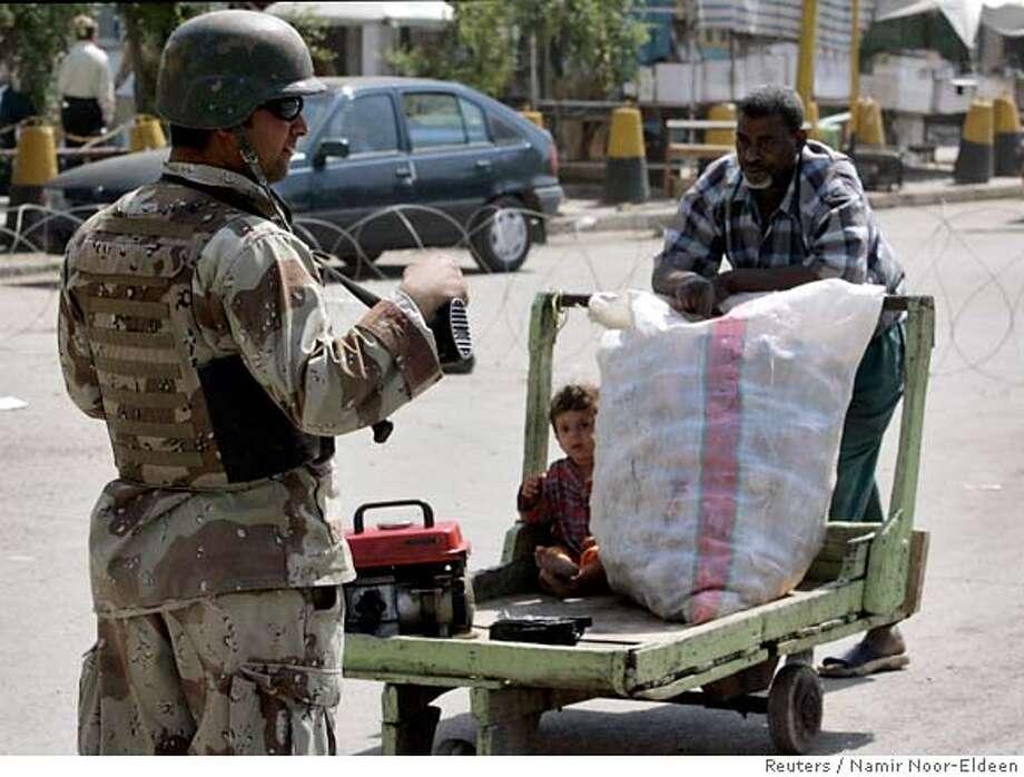 A resident (R) pushes a cart near an Iraqi soldier standing guard at a checkpoint in Baghdad April 1, 2007. REUTERS/Namir Noor-Eldeen (IRAQ) 0 Photo: NAMIR NOOR-ELDEEN