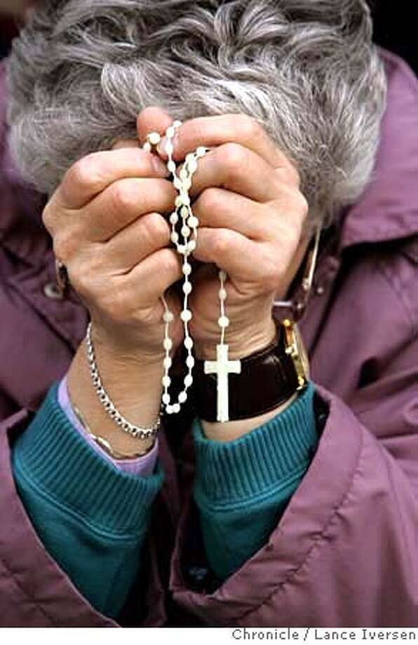 ST. BRIGID_0062.jpg_  Marilyn Aspesi prays on the steps of St. Brigid during the 11th annual vigil. Former parishioners of San Francisco's St. Brigid Church returned to it's parking lot for an early evening mass and dinner, commemorating eleven years after the closure buy the archdiocese. By Lance Iversen/San Francisco Chronicle Photo: Lance Iversen