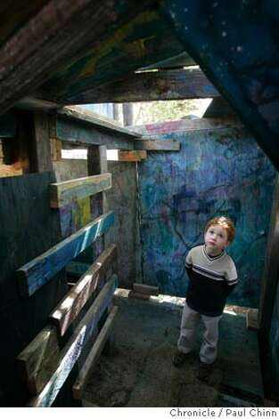 Ian Martin, 4, of San Francisco inspects the inside of a wooden fort at Adventure Playground in Berkeley, Calif. on Saturday, March 10, 2007. Adventure Playground is a unique location where children can play on structures that they actually create and construct using tools provided to them. The playground�s been around since 1979 but the concept began after WW II in Europe. At the Berkeley park, countless pieces of scrap wood, tires, rope and other material is donated and used again-and-again by the kids to construct and dismantle slides, swings and climbing structures.  PAUL CHINN/The Chronicle  **Ian Martin Photo: PAUL CHINN
