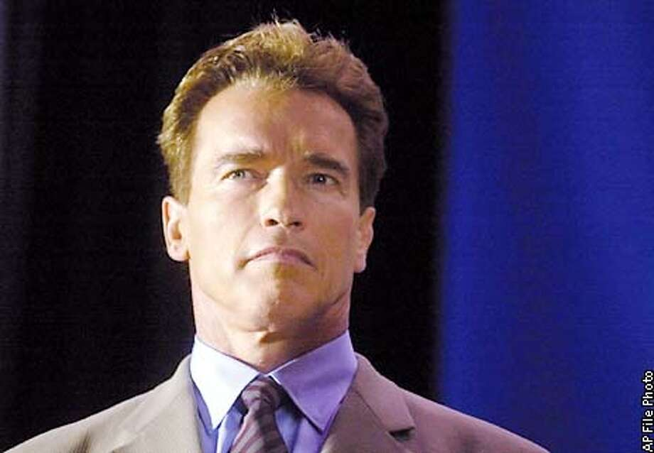 FILE--Actor Arnold Schwarzenegger waits to address a crowd during an awards ceremony in this Aug. 28, 2000 file photo, at Girls & Boys Town in Omaha, Neb. Schwarzenegger is opting out of the 2002 race to become California's governor, saying his film career and family have taken precedence over politics. He said that he was not abandoning the idea of running for office as a Republican, but was only postponing his plunge into politics until his four children, ages 3 to 11, are older, the Times said Wednesday, April 25, 2001. (AP Photo/Dave Weaver, File) Photo: DAVE WEAVER