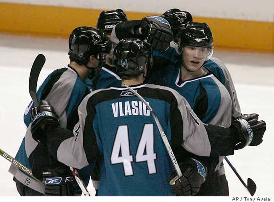 San Jose Sharks' Christian Ehroff, right, of Germany, is congratulated by teammates after scoring a goal against the Phoenix Coyotes in the second period of an NHL hockey game in San Jose, Calif., Friday, March 30, 2007. (AP Photo/Tony Avelar) Photo: Tony Avelar