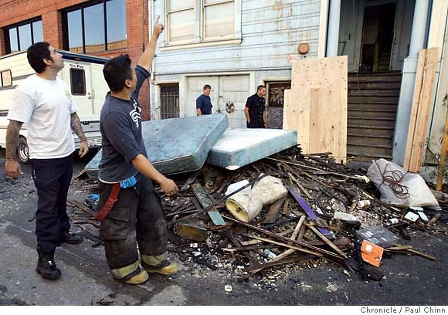 Firefighters returned to the scene to survey the damage after an early morning fire killed one resident on the third floor of an apartment building on Clementina St. on 9/27/05 in San Francisco, Calif.  PAUL CHINN/The Chronicle Photo: PAUL CHINN