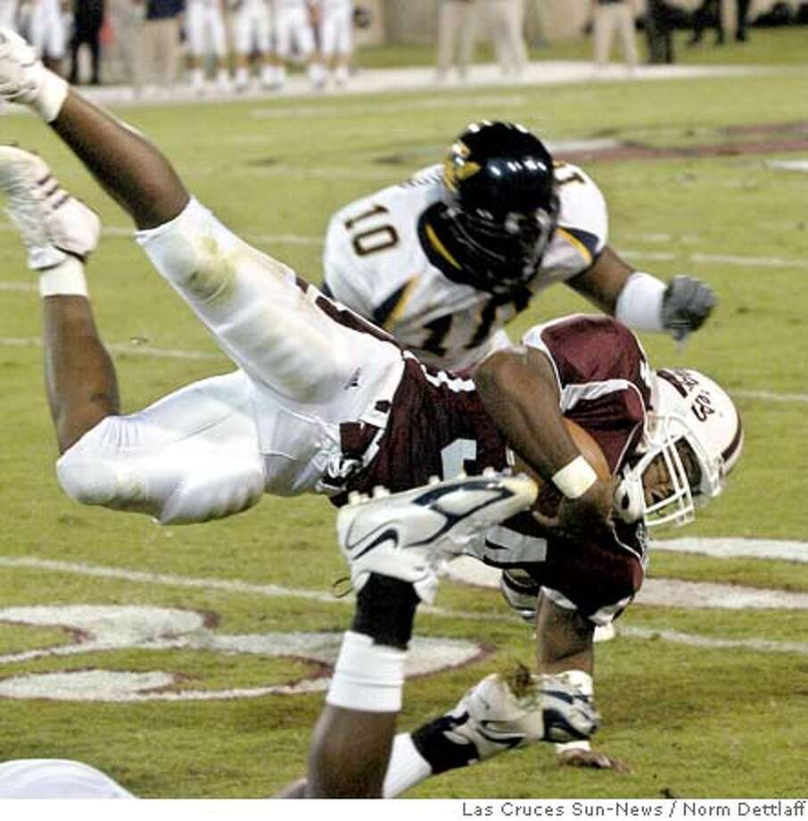 New Mexico State's Justine Buries, front, flies to the ground after being hit by a California player as California's Desmond Bishop (10) runs to make sure he stays down Friday, Sept. 23, 2005, at Aggie Memorial Stadium in Las Cruces, N.M. (AP Photo/Las Cruces Sun-News, Norm Dettlaff) Photo: NORM DETTLAFF