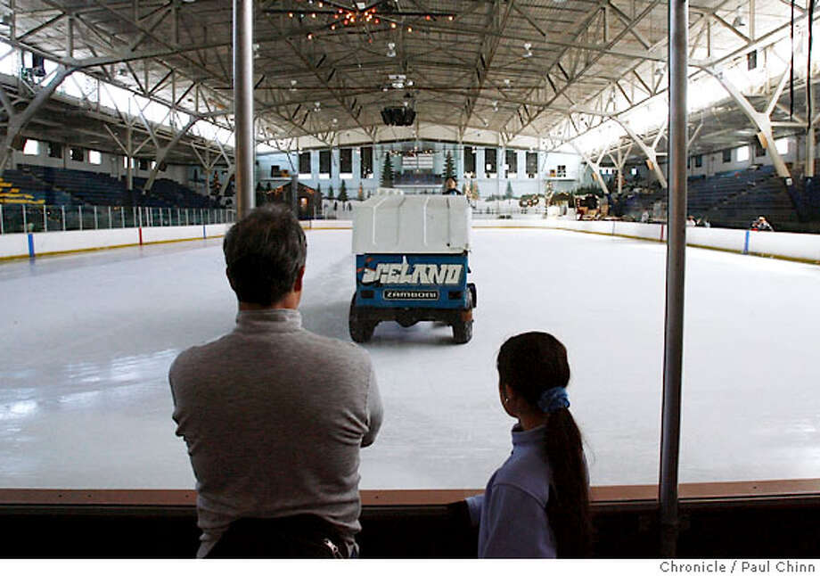 Scott North and his daughter Naomi watch the Zamboni resurface the ice on one of its final laps around the rink at the final public skating session at Iceland in Berkeley, Calif. on Saturday, March 31, 2007. North, who now lives in Osaka, Japan, played youth hockey at Iceland in the late 1960's. Facing rising operational costs, the owners of the 66-year-old rink were forced to shut its doors and melt the ice after attempts to sell the rink came up short. However, a community-led effort is still hoping to scrape enough money together to reopen Iceland.  PAUL CHINN/The Chronicle  **Scott North, Naomi North Photo: PAUL CHINN