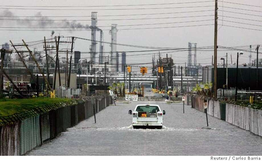 A truck crosses a flooded road at the entry of a refinery in Port Arthur, after hurricane Rita hit coastal communities in Texas and Louisiana September 24, 2005. Hurricane Rita caused an estimated $2.5 billion to $5 billion in insured losses in eastern Texas and western Louisiana, catastrophe risk modeller AIR Worldwide said on Saturday. REUTERS/Carlos Barria Ran on: 09-25-2005  A truck navigates the flooded entry to an oil refinery in Port Arthur, a low-lying Texas city hit hard by Hurricane Rita. The storm caused significant damage at one local refinery. Photo: CARLOS BARRIA