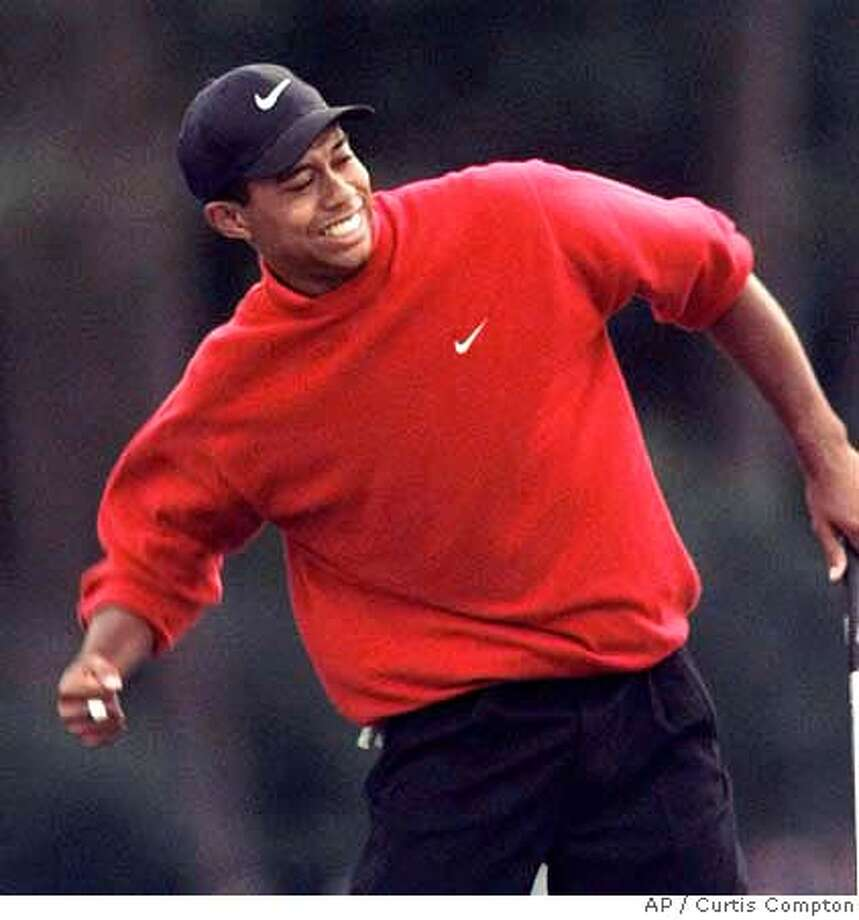 Tiger Woods celebrates as he wins the 1997 Masters with a record-breaking 18-under-par for the tournament at the Augusta National Golf Club in Augusta, Ga., Sunday, April 13, 1997. (AP Photo/ Curtis Compton) ELECTRONIC IMAGE Photo: CURTIS COMPTON