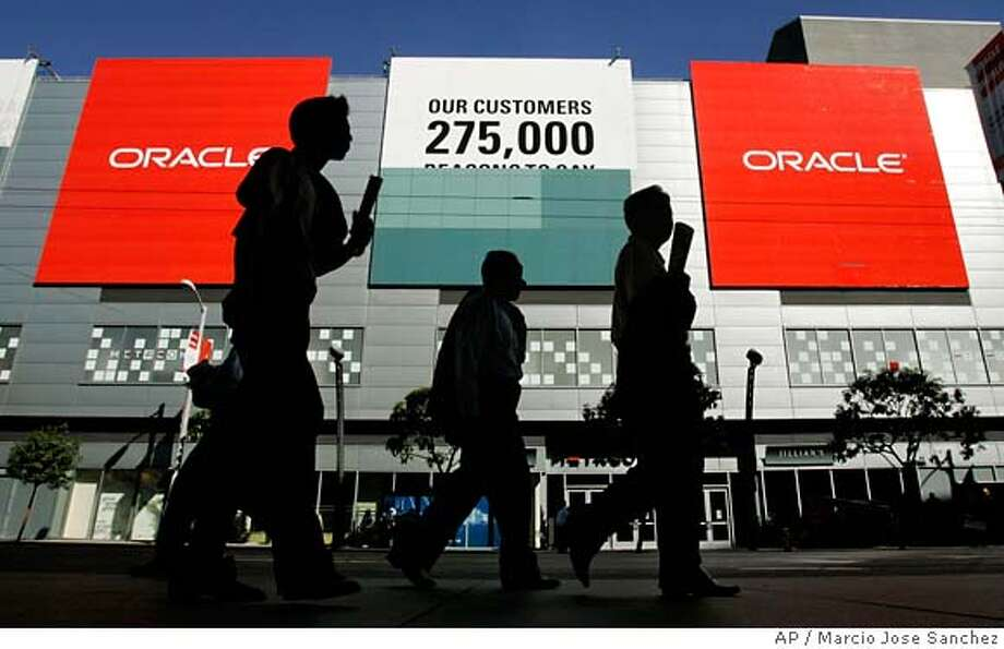 People walk by murals advertising the upcoming Oracle OpenWorld convention at the Moscone Center in San Francisco Friday, Oct. 20, 2006. The convention takes place from Oct. 22-29 and it promotes Oracle's applications and technology. (AP Photo/Marcio Jose Sanchez) STAND ALONE PHOTO Photo: MARCIO JOSE SANCHEZ