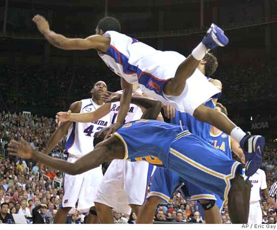 Florida's Taurean Green falls on top of UCLA's Alfred Aboya (12) during the first half of a Final Four semifinal basketball game at the Georgia Dome in Atlanta, Saturday, March 31, 2007. (AP Photo/Eric Gay) Photo: Eric Gay
