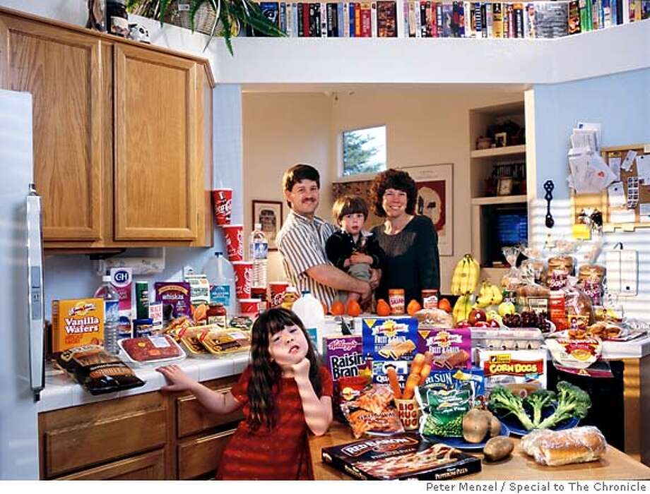 USca01.0001.xxf1s (MODEL RELEASED IMAGE)  The Caven family in the kitchen of their home in American Canyon, California, with a week�s worth of food. Craig Caven, 38, and Regan Ronayne, 42 (holding Ryan, 3), stand behind the kitchen island; in the foreground is Andrea, 5. Cooking methods: electric stove, microwave, outdoor BBQ. Food preservation: refrigerator-freezer, freezer. Favorite foods�Craig: beef stew. Regan: berry yogurt sundae (from Costco). Andrea: clam chowder. Ryan: ice cream. /// The Caven family is one of the thirty families featured in the book Hungry Planet: What the World Eats (p. 260). Food expenditure for one week: $159.18 USD. (Please refer to Hungry Planet book p. 261 for the family�s detailed food list.) Photo: Peter Menzel