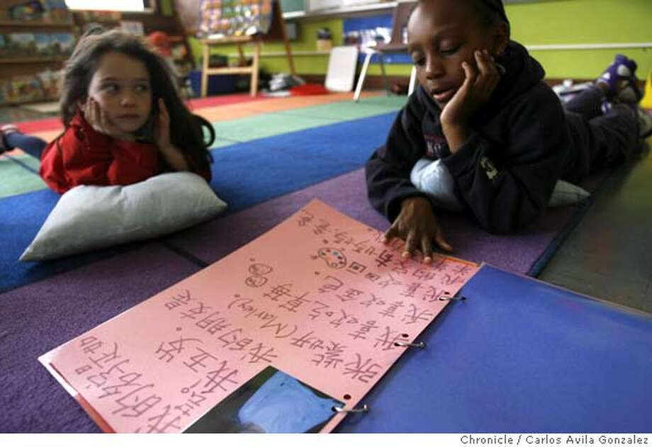 Durrell Laury reads with Lea Pickholtz during a lunch break in kindergarten class on Tuesday, March 20, 2007. The two students are taking part in Starr King Elementary's Mandarin immersion kindergarten class. Durrell Laury is a student in the Starr King kindergarten Mandarin program. He doesn't fit the stereotype. He's African American with no cultural link to China or Mandarin, but his mother and he are thrilled that he's in the class and can already carry on conversations with native speakers. Photo by Carlos Avila Gonzalez/The Chronicle  Photo taken on 3/20/07, in San Francisco, Ca, USA.  **All names cq (source) Photo: Carlos Avila Gonzalez