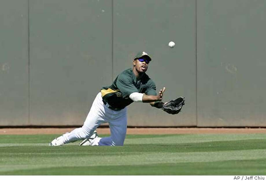 Oakland Athletics' Shannon Stewart tries to catch a double hit by Seattle Mariners' Jose Lopez in the fourth inning of a spring training baseball game in Phoenix, Sunday, March 25, 2007. (AP Photo/Jeff Chiu) Photo: Jeff Chiu