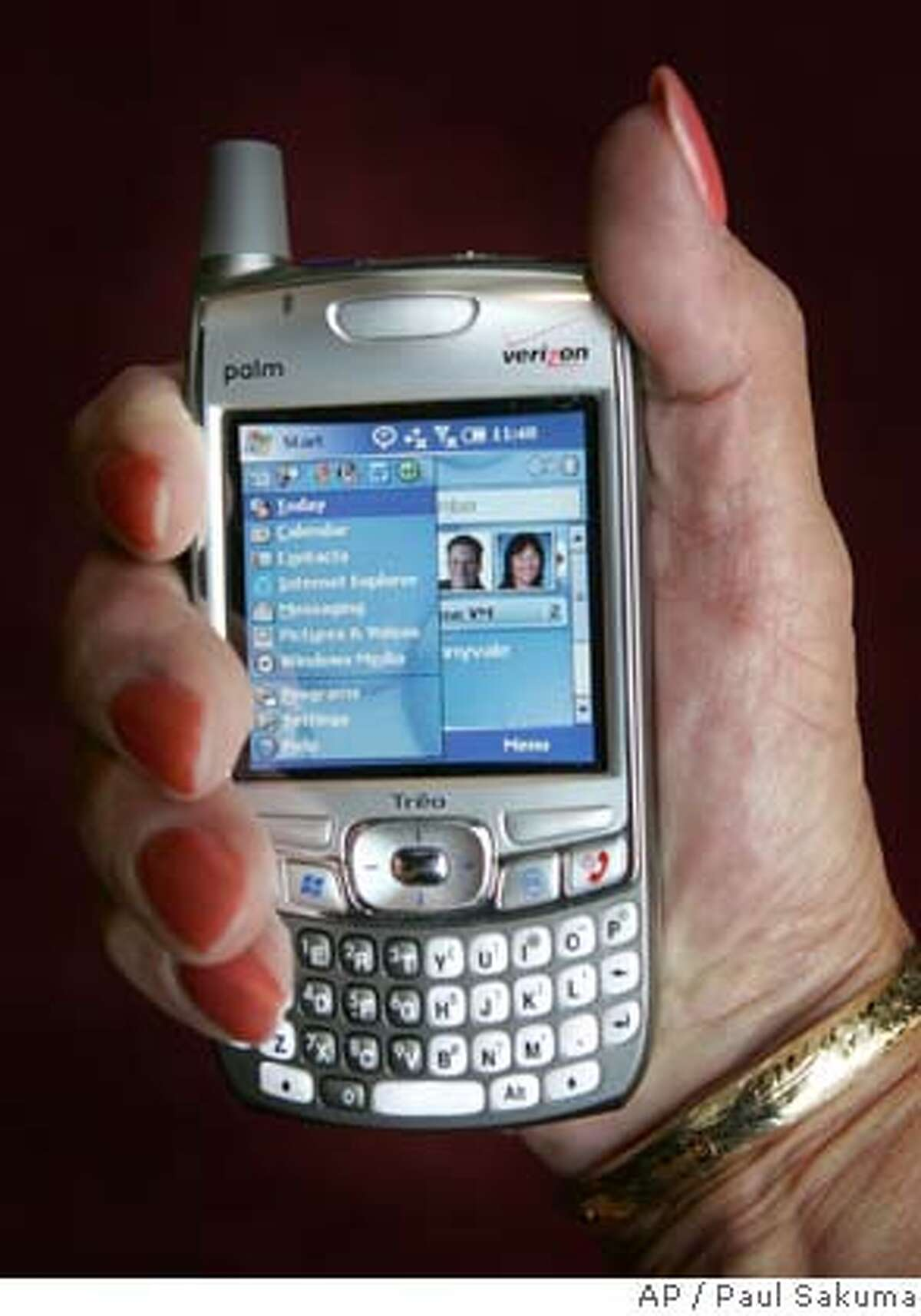 Biruta McShane of Palm Inc., holds up the new Palm Treo smart phone duing a joint news conference with Microsoft Corp., Monday, Sept. 26, 2005 in San Francisco. Palm announced that it has gone into business with former rival Microsoft Corp. to launch a Windows-based Treo smartphone, marking the first time that a Palm product will run on an operating system other than Palm's. (AP Photo/Paul Sakuma)