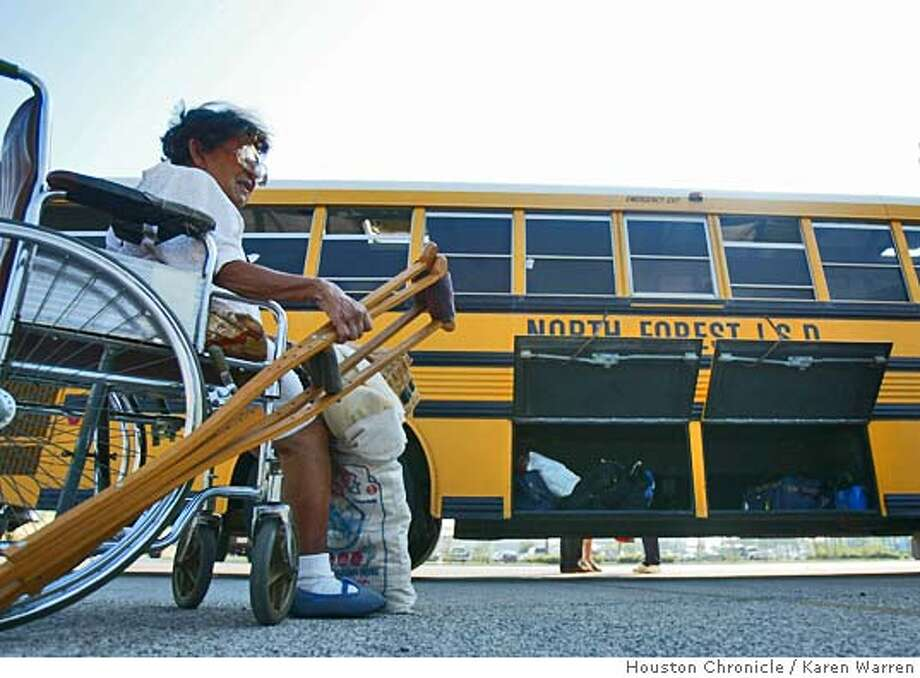 Frances Alvarez waits in the Galveston Convention Center parking lot, to board a school bus Thursday morning, as over 100 residents wait for working buses to arrive to take evacuees to Huntsville, as Galveston prepares for , Thursday, September 22, 2005. (Karen Warren/Houston Chronicle) Photo: Karen Warren