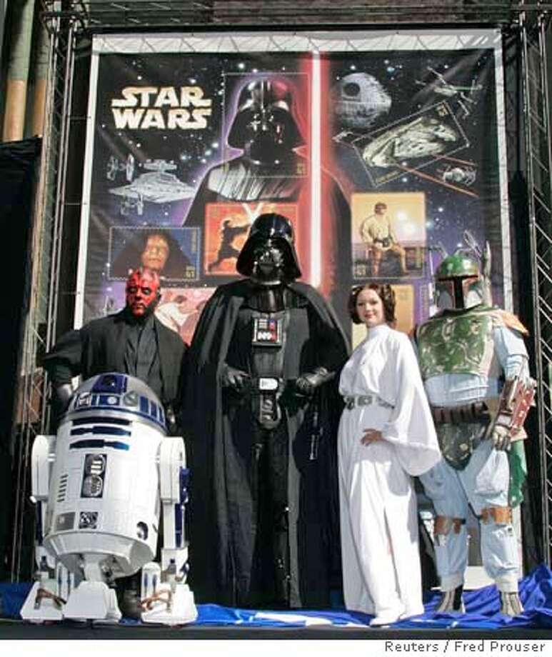 Star Wars characters (L-R) R2D2, Darth Maul, Darth Vader, Princess Leia and Boba Fett pose in front of the newly unveiled designs of the 15 U.S. postage stamps honoring the 30th anniversary of 'Star Wars' characters and films during ceremonies in Hollywood March 28, 2007. The 15 stamps featuring such characters Luke Skywalker, Princess Leia and R2D2 will be released May 25 at a Star Wars fan convention in Los Angeles. REUTERS/Fred Prouser (UNITED STATES) 0 Photo: FRED PROUSER