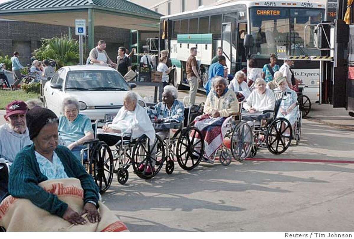 A line of elderly wheel chair bound citizens from the Edgewater Retirement Community in Galveston,Texas, wait to board a bus to evacuate the city in preparation for Hurricane Rita, September 21, 2005. Texas Gov. Rick Perry said on Wednesday a long stretch of his state's Gulf coastline should be evacuated now in advance of Hurricane Rita, which is due to make land on Friday. REUTERS/Tim Johnson
