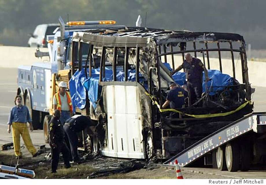 Authorities look for evidence inside the burnt remains of a charter bus that exploded near Dallas, Texas September 23, 2005. A bus carrying elderly Hurricane Rita evacuees from the Houston area burst into flames outside Dallas before dawn on Friday, killing at least 24 people trapped inside, officials said. Multiple explosions were heard before the bus became engulfed in flames, lighting the morning sky near Wilmer, a southern suburb of Dallas, witnesses said. REUTERS/Jeff Mitchell Photo: JEFF MITCHELL