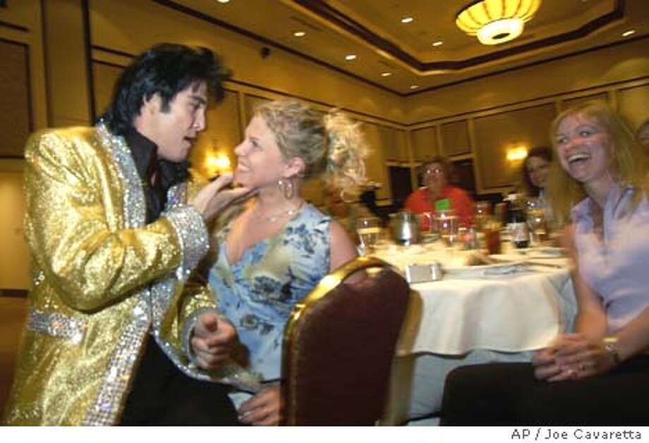 """Elvis impersonator James """"Love"""" Rompel sings to Angela VanBerkel, 17, of Niagara on the Lake, Canada, Thursday, June 26, 2003 at the Rampart Hotel and Casino in Las Vegas. The National Abstinence Network, which promotes virginity, is holding its conference in Sin City this year. (AP Photo/Joe Cavaretta) Photo: JOE CAVARETTA"""