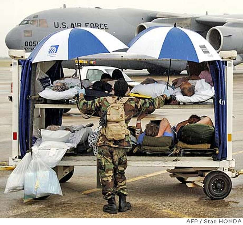 A National Guard soldier protects elderly patients on a luggage cart with umbrellas before they are transported to a waiting C-17 cargo plane (rear), 23 September, 2005, as they are evacuated from the Port Arthur, Texas, area airport in advance of Hurricane Rita. Some one million people have left the area around Houston ahead of powerful Hurricane Rita, including about 15,000 who were helped out by authorities, city officials said Friday. AFP PHOTO/Stan HONDA (Photo credit should read STAN HONDA/AFP/Getty Images) [Photo via NewsCom] Photo: STAN HONDA