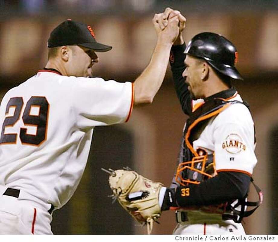 Giants's catcher, Benito Santiago, right, high fives pitcher, Jason Schmidt after the Giants beat the Dodgers 2-1. San Francisco Giants play the Los Angeles Dodgers at Pac Bell Park on Monday, June 24, 2003. Event on 06/24/03 in San Francisco, CA. Photo By CARLOS AVILA GONZALEZ / The San Francisco Chronicle Photo: CARLOS AVILA GONZALEZ