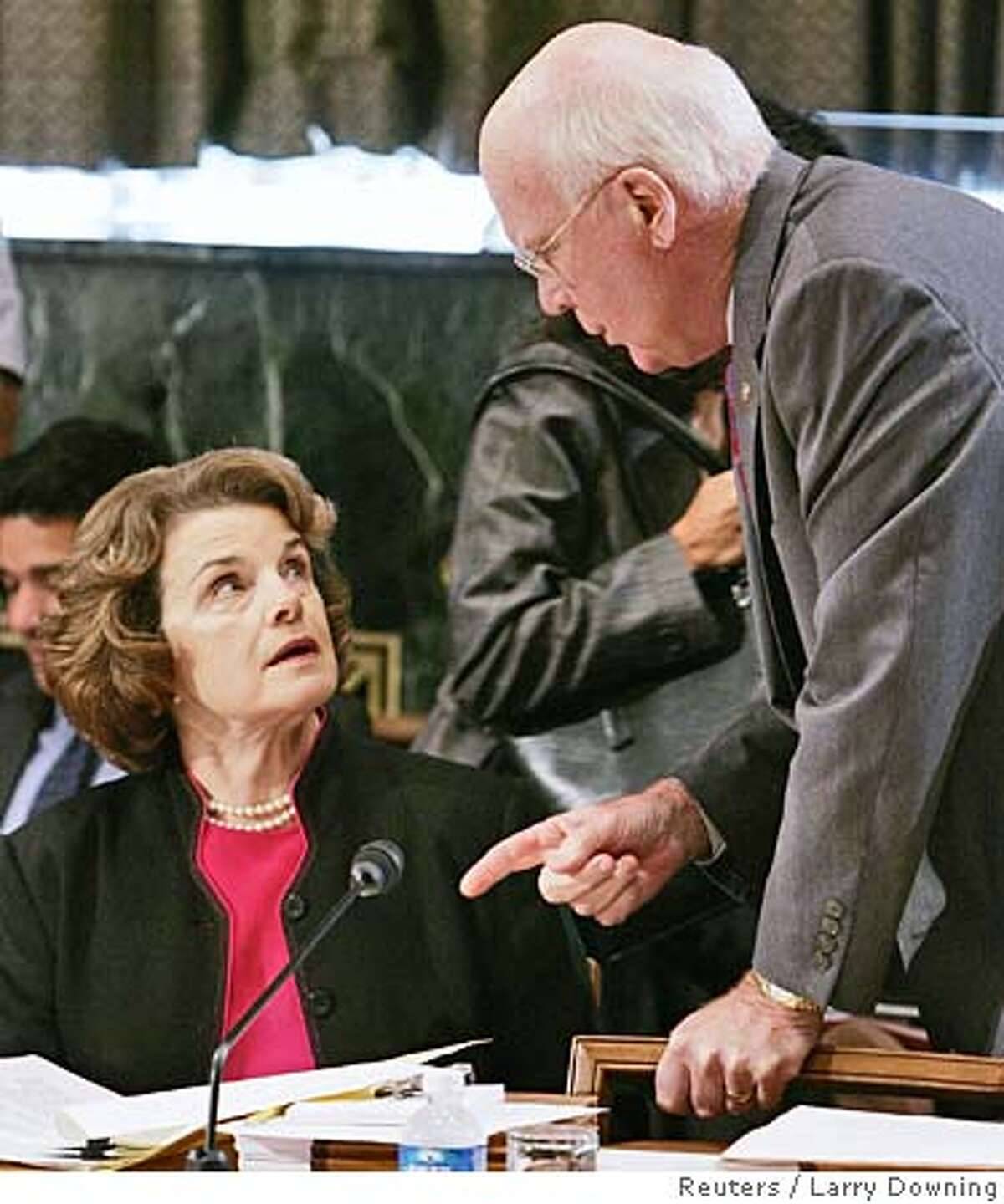 Ranking Senate Judiciary Committee Democratic U.S. Senator Patrick Leahy (D-VT) (R), confers with U.S. Senator Dianne Feinstein (D-CA) before he speaks in favor of the nomination of John Roberts to be Chief Justice of the Supreme Court during the Senate Judiciary Committee mark-up hearings on Capitol Hill in Washington September 22, 2005. U.S. Senate leaders warned President George W. Bush on Wednesday his next Supreme Court nominee will likely face a far more contentious confirmation battle than conservative John Roberts, who is poised to become U.S. chief justice. Feinstein announced she would not support Roberts for the position. REUTERS/Larry Downing 0