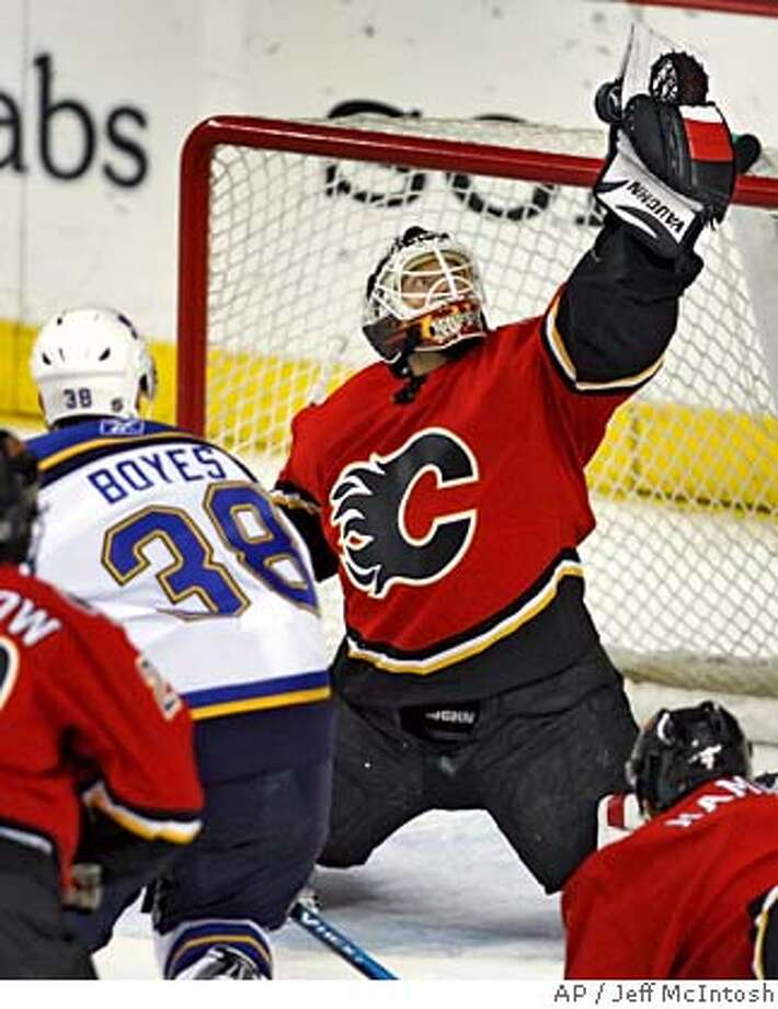 Calgary Flames goalie Mikka Kiprusoff, right, struggles to hang onto the puck as St. Louis Blues' Brad Boyes looks for a rebound during overtime NHL hockey action in Calgary, Monday, March 12, 2007. The Flames beat the Blues 5-4 in a shootout.(AP PHOTO/CP, Jeff McIntosh) Canada Photo: Jeff McIntosh