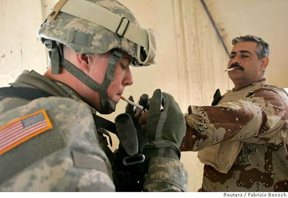 An Iraqi army soldier (R) lights the cigarette of a U.S. soldier during a medical mission conducted by U.S. military doctors for local residents, inside a school in Baghdad's northwest Sunni neighborhood of Ghazaliyah March 25, 2007. REUTERS/Fabrizio Bensch (IRAQ) 0 Photo: FABRIZIO BENSCH