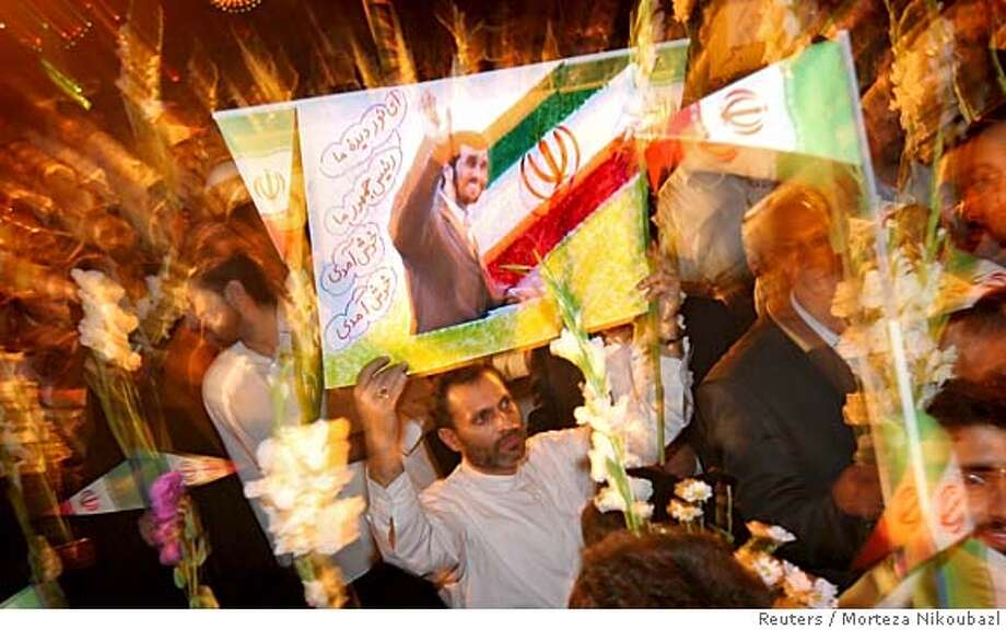 An Iranian supporter holds a picture of Iran's President Mahmoud Ahmadinejad during a public welcoming ceremony at the International Mehrabad Airport in Tehran September 18, 2005. The European Union's three biggest powers began drafting a resolution on Sunday urging the U.N. nuclear watchdog to report Tehran to the Security Council for possible sanctions, EU diplomats said. Ahmadinejad is back in Iran after his five-day trip to New York to attend the 60th General Assembly of the United Nations. REUTERS/Morteza Nikoubazl 0 Photo: Morteza Nikoubazl