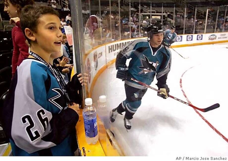 Chris Koukis, left, watches as the San Jose Sharks' Mark Smith, right, skates by before the start of a pre-season game against the Los Angeles Kings on Sunday, Sept. 18, 2005. (AP Photo/Marcio Jose Sanchez) Photo: MARCIO JOSE SANCHEZ