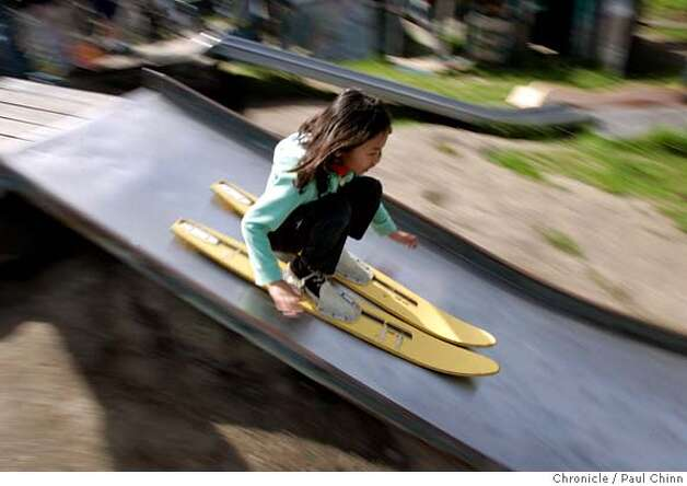 Ruby Bomford, 9, slips down a slide using an old pair of water skis at Adventure Playground in Berkeley, Calif. on Saturday, March 10, 2007. Adventure Playground is a unique location where children can play on structures that they actually create and construct using tools provided to them. The playground�s been around since 1979 but the concept began after WW II in Europe. At the Berkeley park, countless pieces of scrap wood, tires, rope and other material is donated and used again-and-again by the kids to construct and dismantle slides, swings and climbing structures.  PAUL CHINN/The Chronicle  **Ruby Bomford MANDATORY CREDIT FOR PHOTOGRAPHER AND S.F. CHRONICLE/NO SALES - MAGS OUT Photo: PAUL CHINN