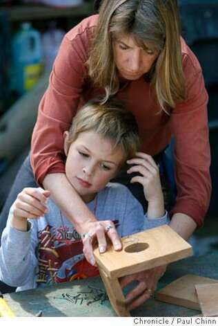 Karen Ford helps her son Matthew build a birdhouse at Adventure Playground in Berkeley, Calif. on Saturday, March 10, 2007. Adventure Playground is a unique location where children can play on structures that they actually create and construct using tools provided to them. The playground�s been around since 1979 but the concept began after WW II in Europe. At the Berkeley park, countless pieces of scrap wood, tires, rope and other material is donated and used again-and-again by the kids to construct and dismantle slides, swings and climbing structures.  PAUL CHINN/The Chronicle  **Karen Ford, Matthew Ford Photo: PAUL CHINN