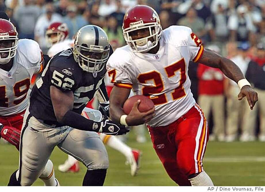 OKansas City Chiefs' Larry Johnson (27) breaks the tackle off Oakland Raiders' linebacker Kirk Morrison (52) in the second quarter Sunday, Sept. 18, 2005, in Oakland, Calif. (AP Photo/Dino Vournas) Photo: DINO VOURNAS