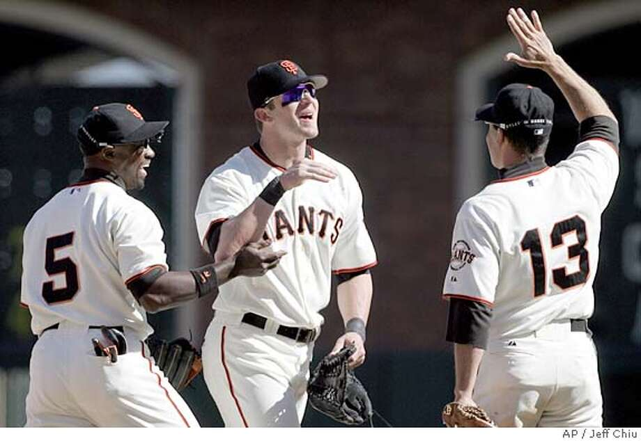 San Francisco Giants' from left, Ray Durham, Daniel Ortmeier, and Omar Vizquel celebrate after beating the Los Angeles Dodgers 2-1 in San Francisco on Saturday, Sept. 17, 2005. (AP Photo/Jeff Chiu) Photo: JEFF CHIU